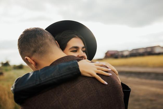 Chiuda in su della bella giovane signora sorridente in cappello nero che abbraccia il suo ragazzo e lo tiene stretto negli abbracci.