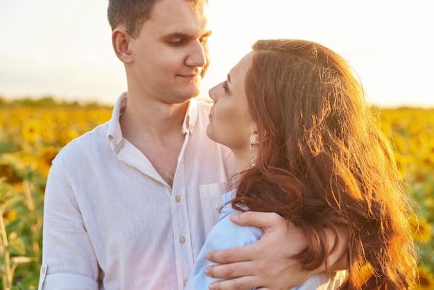 Primo piano di una coppia felice sorridente che abbraccia in un campo di girasoli