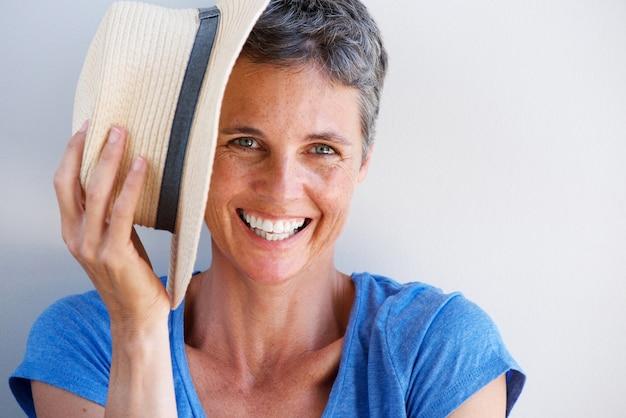 Chiuda sulla donna matura sorridente con il cappello contro la parete bianca
