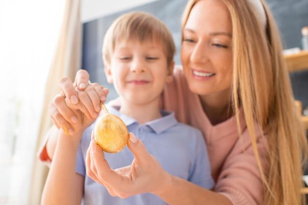 Primo piano della madre sorridente usando il pennello mentre insegna al figlio a disegnare sull'uovo di pasqua