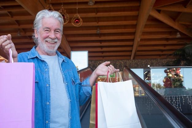 Primo piano di un uomo anziano sorridente dai capelli bianchi che fa shopping per natale in un centro commerciale, guardando la telecamera mentre tiene in mano molte borse con regali per la famiglia e gli amici