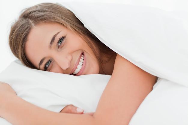 Primo piano, donna sorridente a letto con la testa sul cuscino