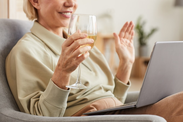 Primo piano della donna sorridente che beve vino e che parla in linea con la sua amica utilizzando il computer portatile a casa