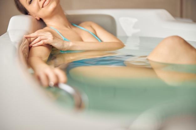 Primo piano su una giovane donna sorridente in bikini che fa un bagno caldo rilassante