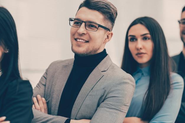 Avvicinamento. sorridente giovane uomo in piedi tra i suoi colleghi. concetto di affari