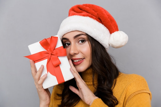 Close up sorridente giovane donna che indossa il cappello di natale in piedi isolato su sfondo grigio, tenendo presente la casella