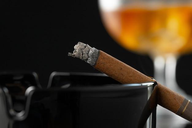 Chiuda in su del fumo di sigaro e bicchiere di whisky sul tavolo