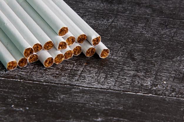 Primo piano di una sigaretta fumante su uno sfondo scuro. foglie di tabacco tritate nei sigari. cattiva abitudine