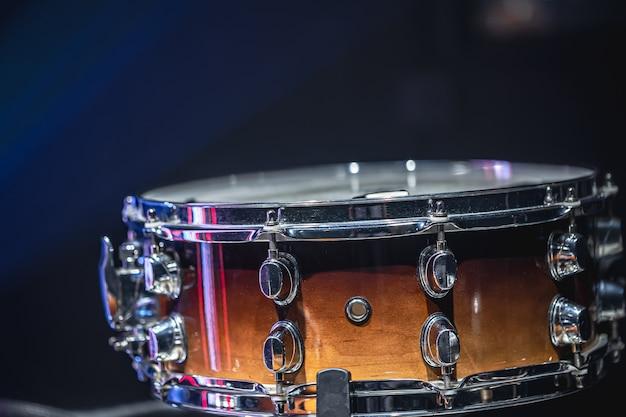 Primo piano di un rullante, strumento a percussione su uno sfondo scuro con foschia, bella illuminazione.