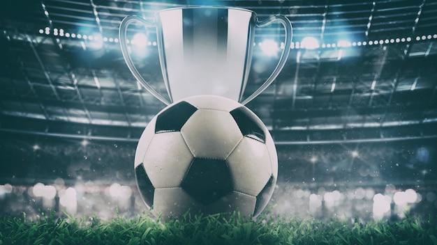 Primo piano di un pallone da calcio con trofeo al centro dello stadio illuminato dai fari