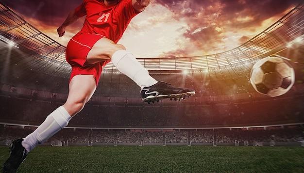 Primo piano di una scena di calcio durante una partita con un giocatore in uniforme rossa che calcia il pallone con forza Foto Premium