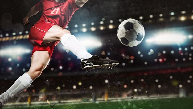 Primo piano di una scena di calcio durante una partita notturna con un giocatore in uniforme rossa che calcia la palla con forza