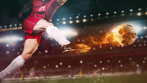 Primo piano di una scena di calcio durante una partita notturna con un giocatore in uniforme rossa che calcia una palla infuocata con potenza