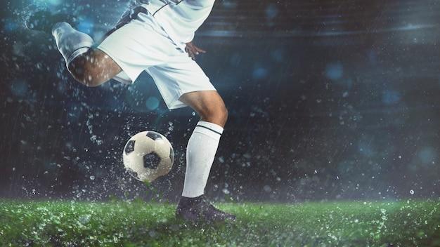 Primo piano di una scena di calcio di notte partita con il giocatore in uniforme bianca calciare la palla con potenza