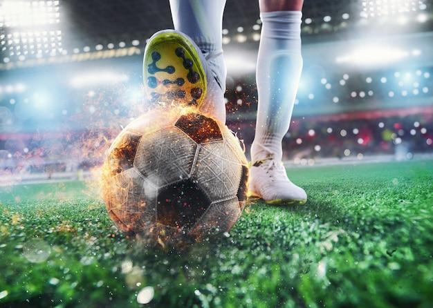 Primo piano di un attaccante di calcio pronto a calciare la palla infuocata allo stadio