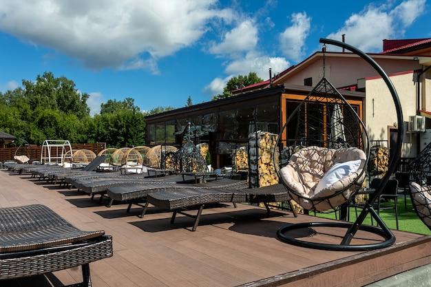 Primo piano di una morbida sedia sospesa all'aperto e di sedie a sdraio in un luogo pubblico in una calda giornata estiva