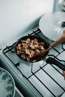 Un primo piano di un po 'di cibo vegano di tofu in padella mentre si cucina in cucina