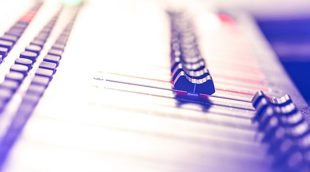 Primo piano, pannello di controllo del mixer audio musicale su sfondo sfocato.