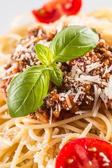 Close-up spaghetti alla bolognese con basilico parmigiano e pomodori.