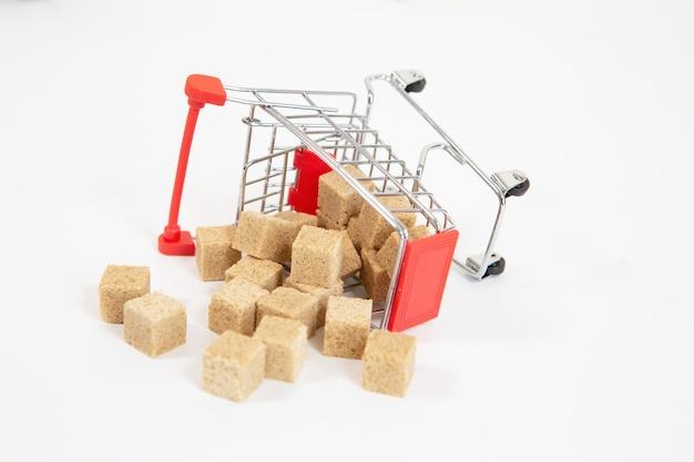 Primo piano su cubetti di zucchero versati da un carrello del supermercato caduto isolato