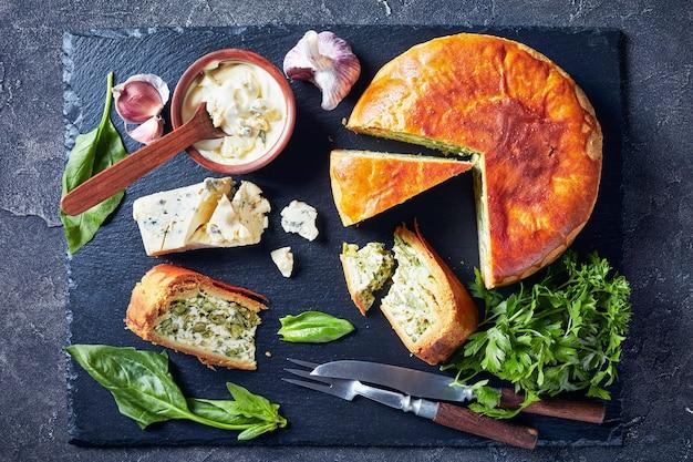 Close-up di spinaci fagiolini e torta di formaggio blu affettato su un vassoio di ardesia nera con salsa di crema di formaggio blu in una ciotola su un tavolo di cemento, vista orizzontale dall'alto