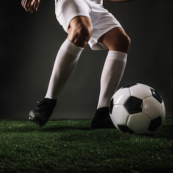 Sportivo del primo piano che dà dei calci alla palla