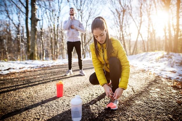 Chiuda su della donna esile attiva sportiva in abiti sportivi che si inginocchiano sulla strada e che legano i laccetti nella mattina soleggiata dell'inverno fuori in natura con un istruttore dietro lei.