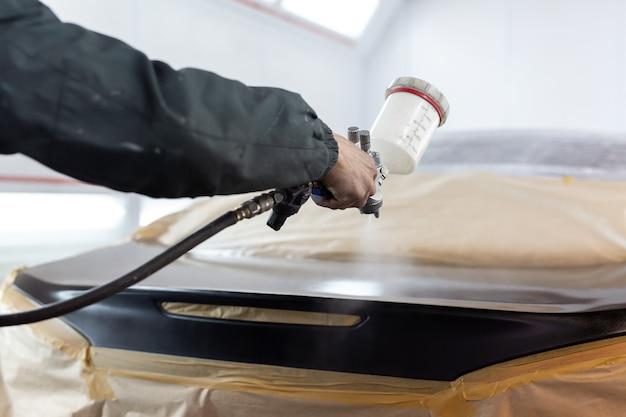 Primo piano di una pistola a spruzzo con vernice nera per la verniciatura di un'auto in una cabina speciale