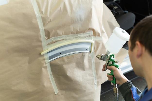 Primo piano di una pistola a spruzzo con vernice bianca per la verniciatura di un'auto in una cabina speciale