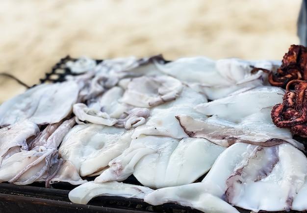 Close-up di calamari nelle mani di un uomo fritto su una griglia sulla riva dell'oceano. il concetto di cucinare e mangiare sano.