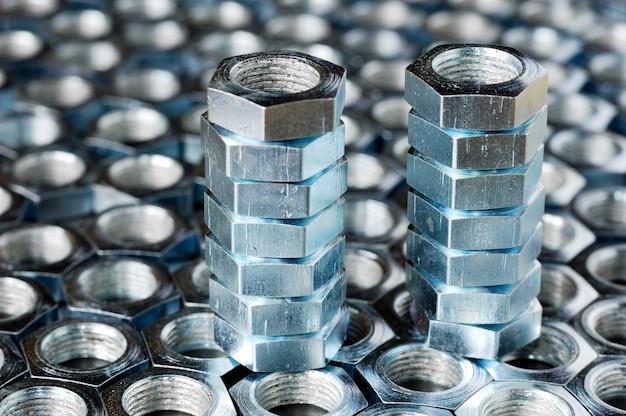 Primo piano di una pila di dadi in metallo cromato stare sui dadi sdraiati sotto forma di favi uno accanto all'altro. il concetto di riparazione di elementi di fissaggio e piccole parti di produzione