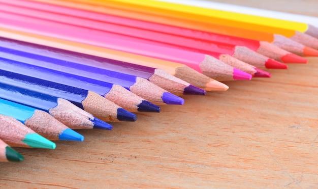 Chiuda sulle matite di colore della pila su fondo di legno