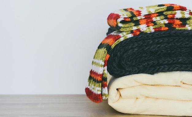 Chiuda sulla pila di vestiti invernali piegati sulla tavola di legno con lo spazio bianco della copia del fondo
