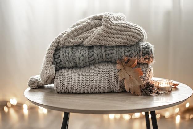 Primo piano di una pila di maglioni lavorati a maglia su uno sfondo sfocato.