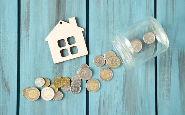 Close-up di monete impilate e figurine di casa su una superficie di legno, concetto di risparmio.