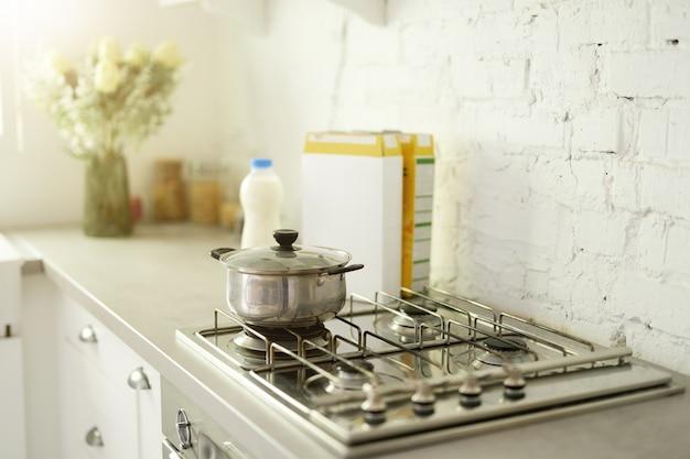 Primo piano della pentola di cottura in acciaio inossidabile sul fornello a gas nella cucina domestica moderna contemporanea. messa a fuoco selettiva. mattina, cucinando il concetto di colazione