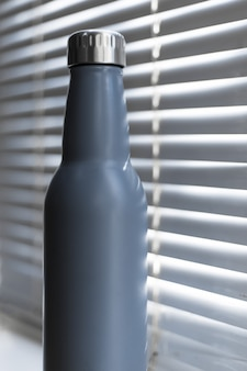 Close-up di acciaio, eco riutilizzabile termo bottiglia d'acqua sullo sfondo della finestra con persiana.