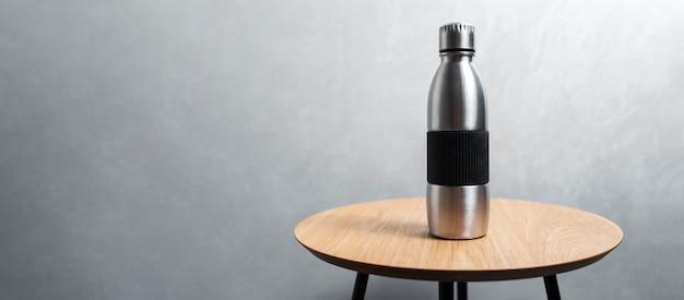Primo piano della bottiglia d'acqua termica riutilizzabile in acciaio sul tavolo di legno sullo sfondo di una parete grigia testurizzata. vista panoramica del banner con spazio di copia.