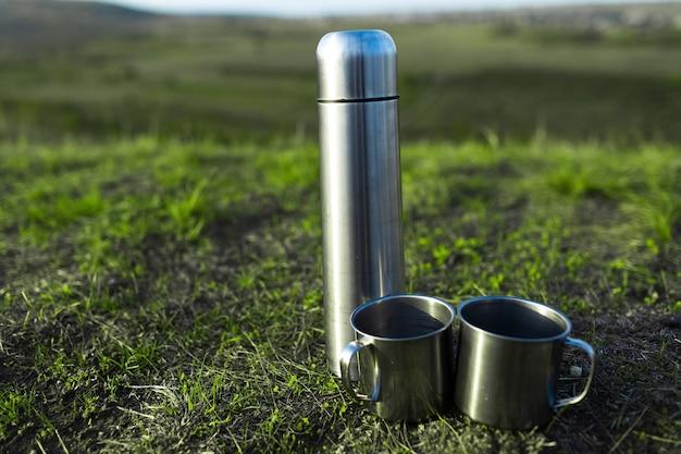 Close-up di thermos in acciaio inox e due tazze su erba verde.