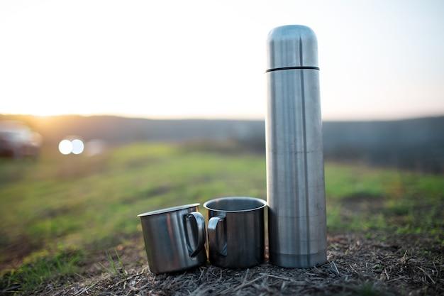 Close-up di thermos in acciaio e due tazze in acciaio inox su erba verde al tramonto.