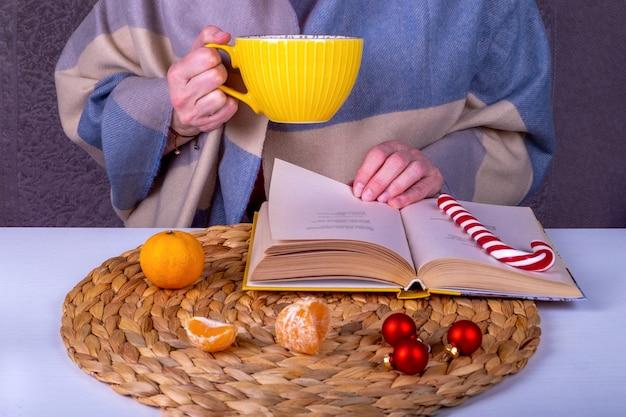Close-up ancora in vita con un libro, decorazioni natalizie sul tavolo. una donna di mezza età con una stola tiene in mano una grande tazza gialla di bevanda calda.