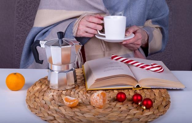Close-up ancora in vita con un libro, una macchinetta del caffè geyser, decorazioni natalizie sul tavolo.