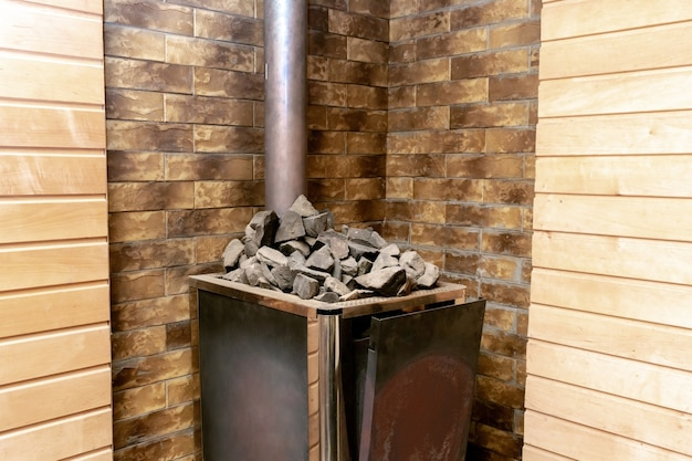 Primo piano di pietre e fornello elettrico a gas nella sauna russa in legno, stabilimento balneare con luce soffusa, riscaldatore interno in pietra e pietre e camino o tubo.