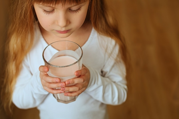 Primo piano del frappè dolce alla fragola nelle mani di una ragazza prescolare carina rossa. una sana colazione gustosa per un bambino.