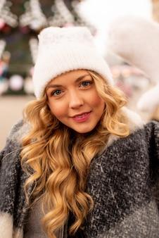 Close up street ritratto di sorridente bella giovane donna sulla festa di natale in fiera. signora che indossa vestiti lavorati a maglia invernali alla moda classici. modello che guarda l'obbiettivo.
