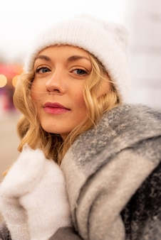 Close up street ritratto di sorridente bella giovane donna sulla festa di natale in fiera. signora che indossa vestiti lavorati a maglia invernali alla moda classici.