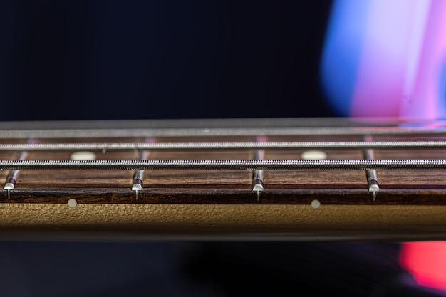 Close-up di stringhe sulla tastiera di un basso su uno sfondo scuro sfocato.