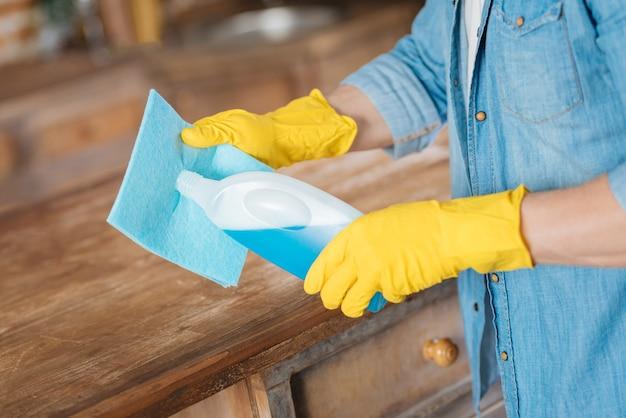 Primo piano di forti mani maschili che indossano guanti gialli che tengono il detergente e lo mettono nel panno per la pulizia