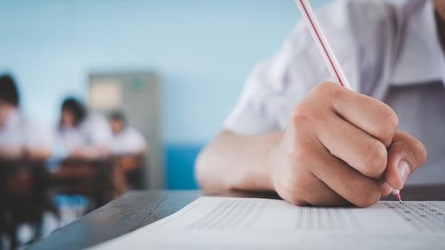 Vicino agli studenti che scrivono e leggono gli esercizi dei fogli di risposta degli esami in aula della scuola con lo stress