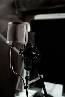 Primo piano microfono a condensatore da studio con filtro anti-pop e supporto antivibrante per la registrazione dal vivo